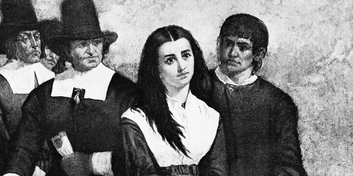 an illustration of a few men taking a suspected witch into custody.