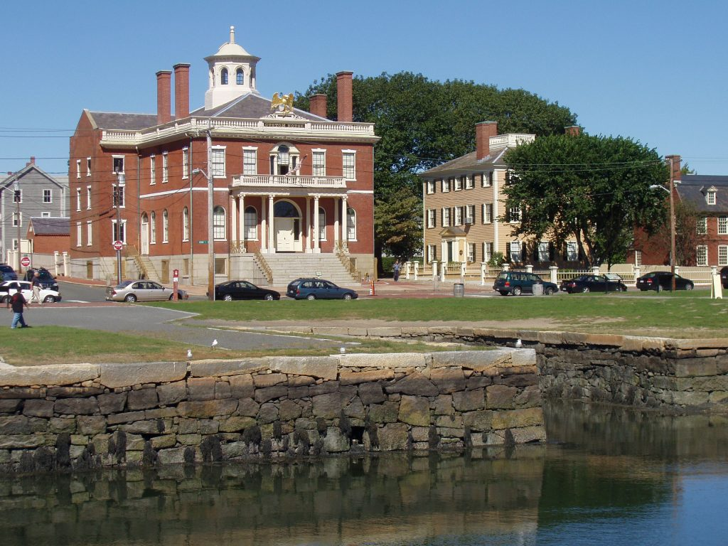 photo shows a large brick building, known as the custom house right near the water's edge.