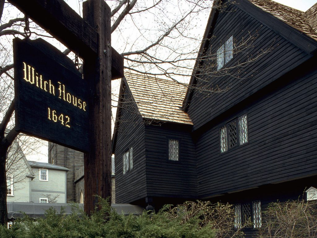 "photo shows the exterior of the salem witch house and a sign that reads ""salem witch house, 1642."""