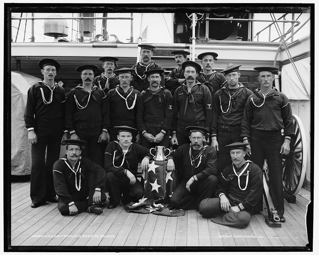 Photo is black and white, and shows a group of 15 sailors on a ship standing together.