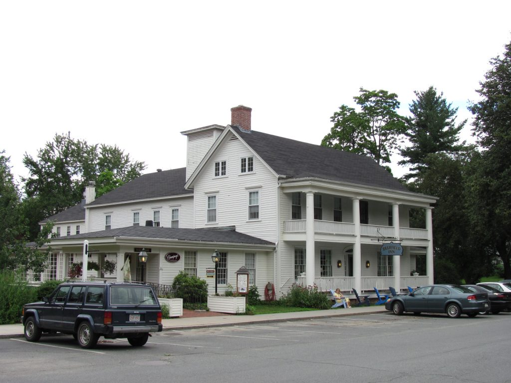 photo shows the facade of the Deerfield inn from the parking lot. the large double story porches are also seen.